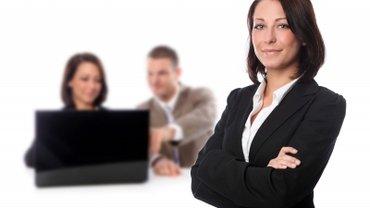 Geschäftsfrau blickt selsbtbewusst in die Kamera