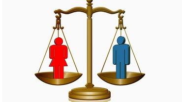 Ein Mann und eine Frau stehen in den zwei gegenüberliegenden Schalen einer Waage, die im Gleichgewicht liegt